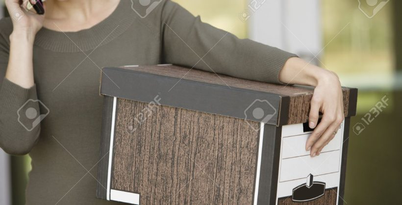 20716707-Businesswoman-Using-Mobile-Phone-with-Moving-Box-Stock-Photo