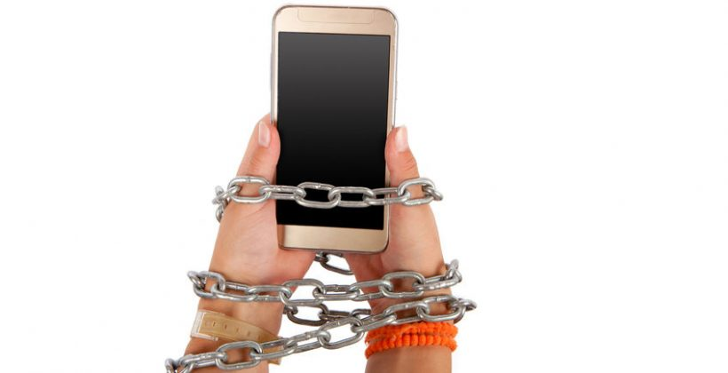 63752832 - chained hands of a child holding a smartphone with a gradient gray screen. smartphone, internet addiction concept. studio isolated on white background.